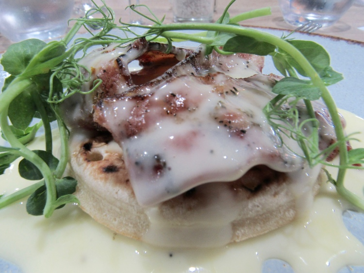 A crumpet with bacon and rocket covered in a cheese sauce
