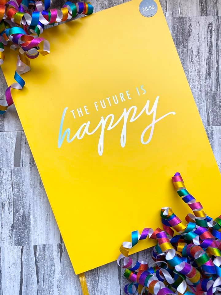 A yellow b6 notebook with the quote the future is happy in silver foiling with multi coloured confetti