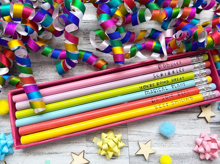pencils with slogan with multicolour confetti wooden stars and coloured bows