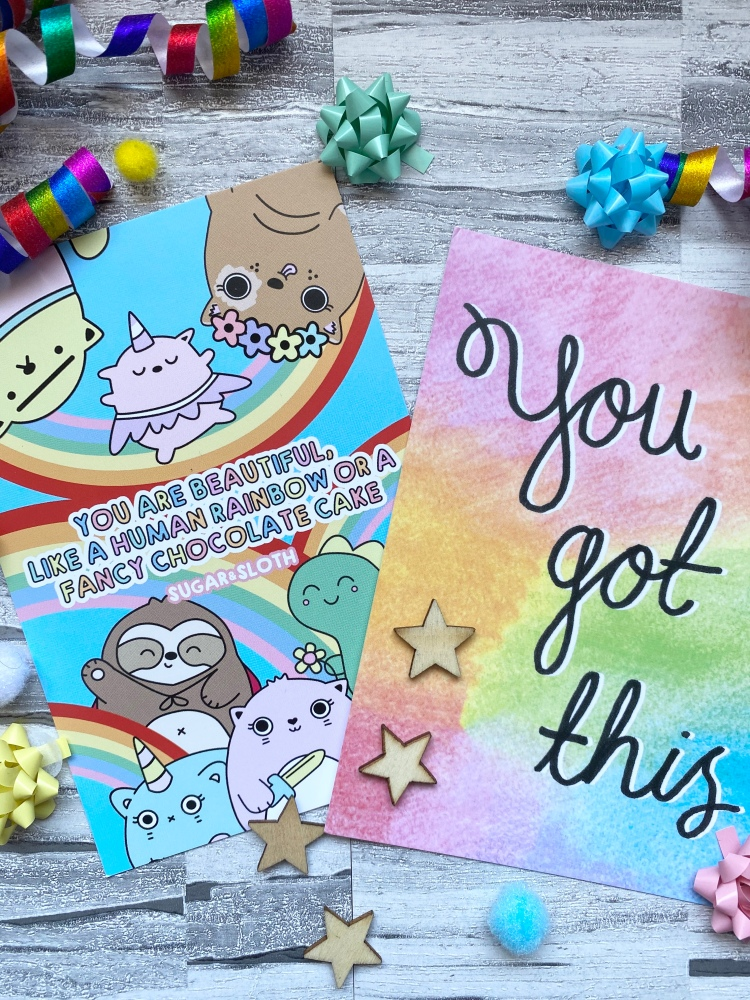 postcards with positive messages, multicolour confetti and coloured present bows and wooden stars
