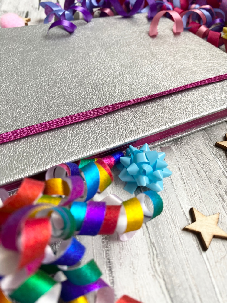 silver bullet journal with bright pink strap and pink page edging with wooden stars and coloured confetti