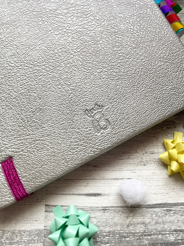 a silver bullet journal with a pink strap, coloured dots and busy embossed logo
