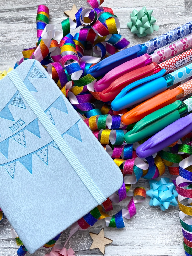 coloured pens with a small blue notebook with wooden stars and multi coloured confetti