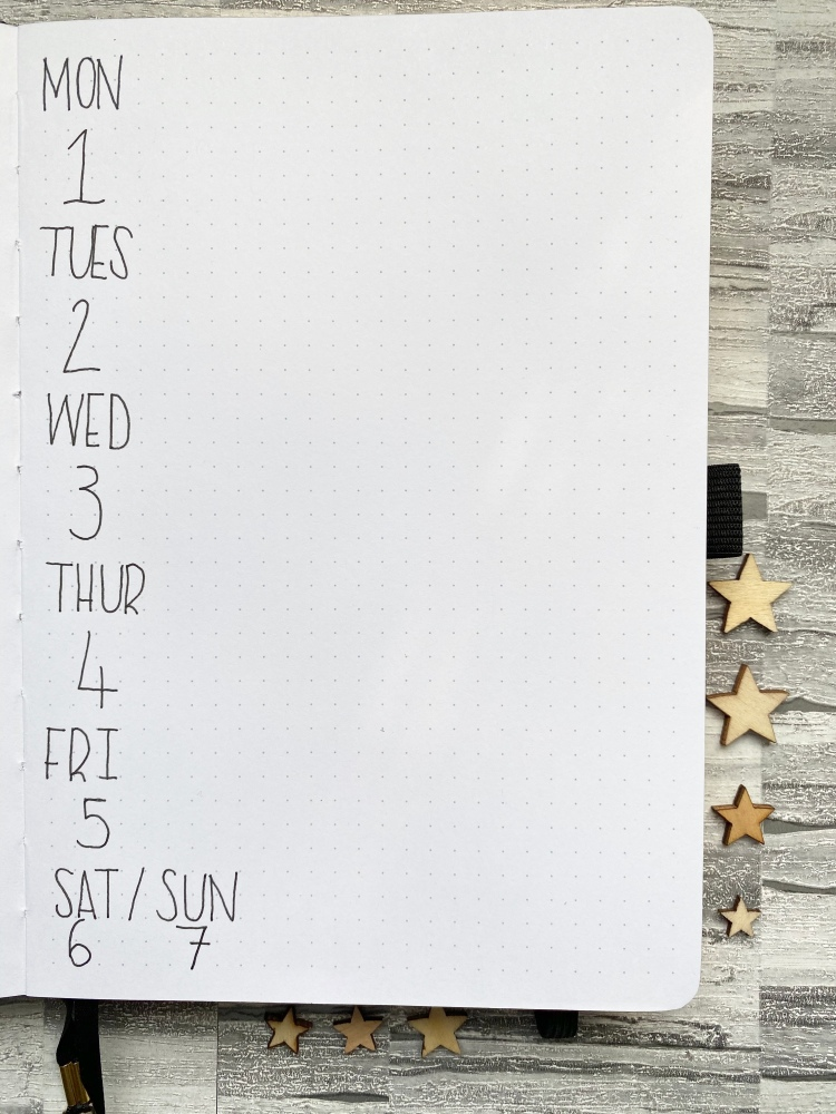 a weekly bullet journal spread, with blank ink and wooden stars