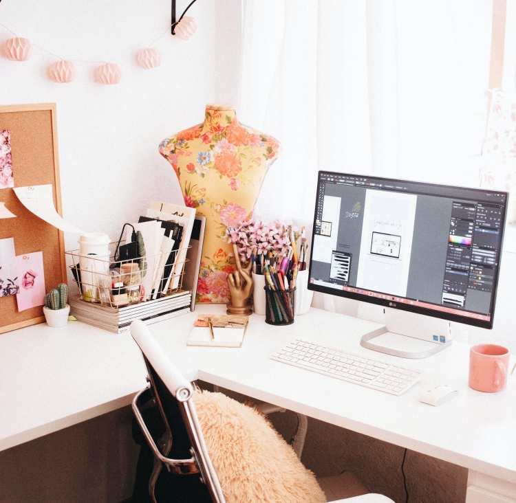 An LG desktop on a white desk with a cork board pen pots and a pink mug