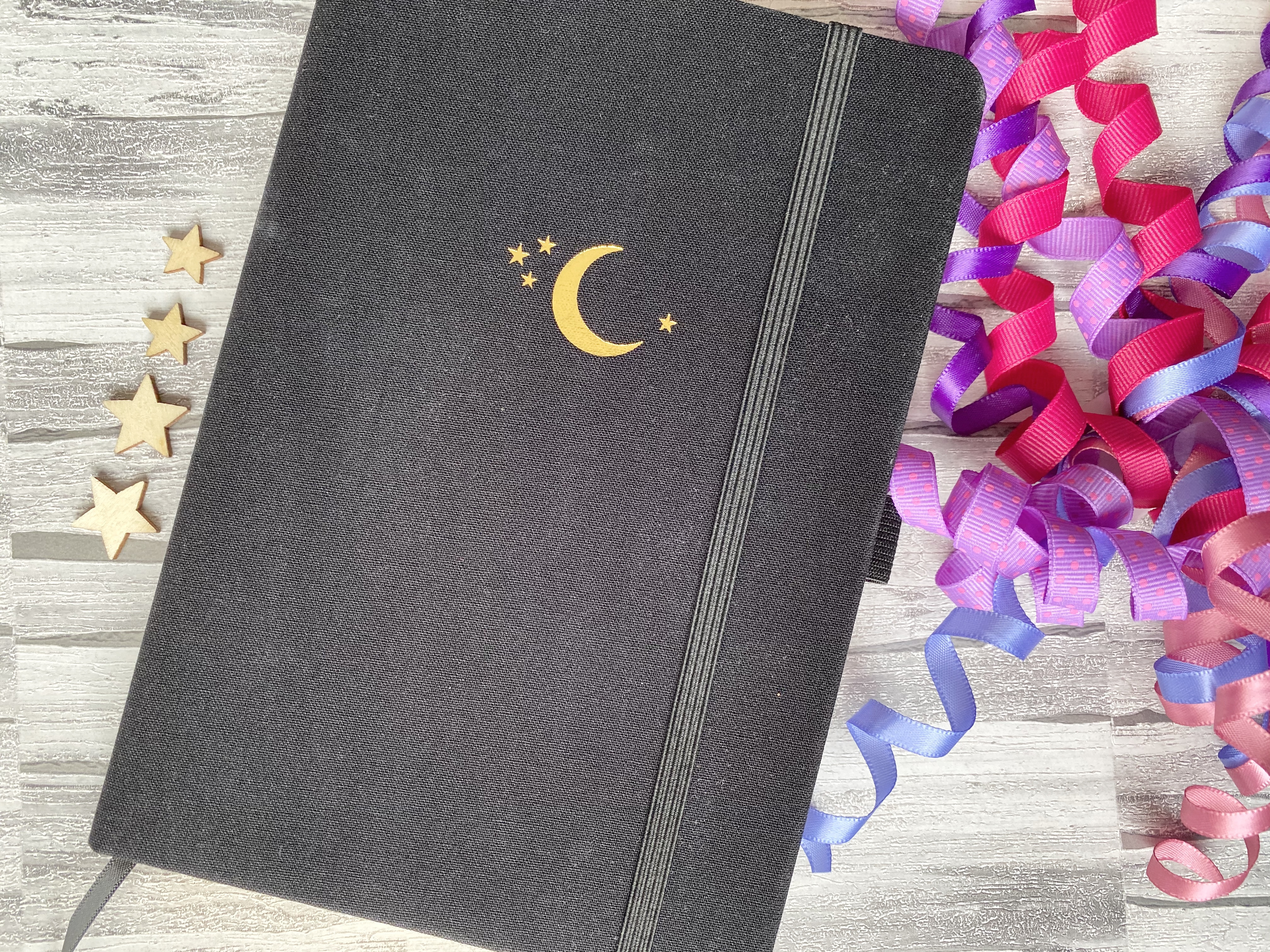 archer and olive black bullet journal with gold moon and stars with wooden stars and pink confetti