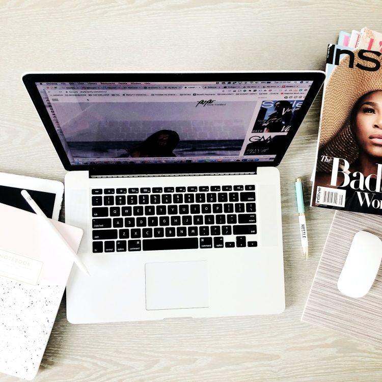 wooden desk with macbook, magazines and notebook an iPad and a white mouse with a hustle slogan pen