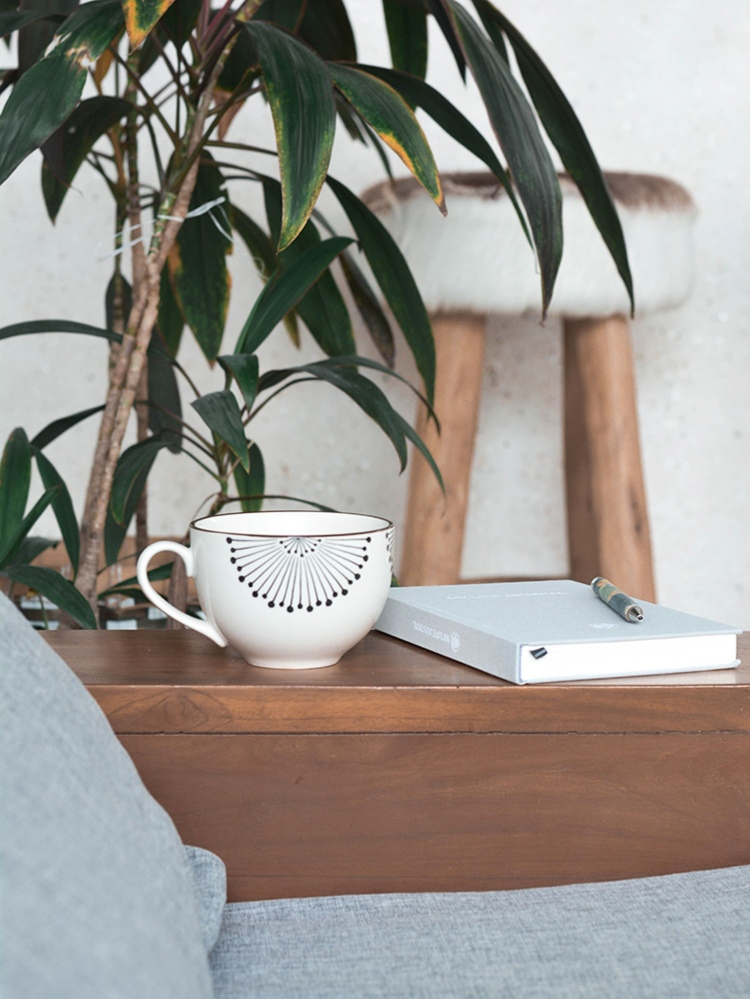 a wooden bedside table with a journal, a china mug and a plant