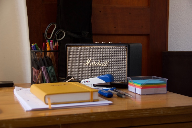 A desk set up with office supplies, a radio, a notebook and pens