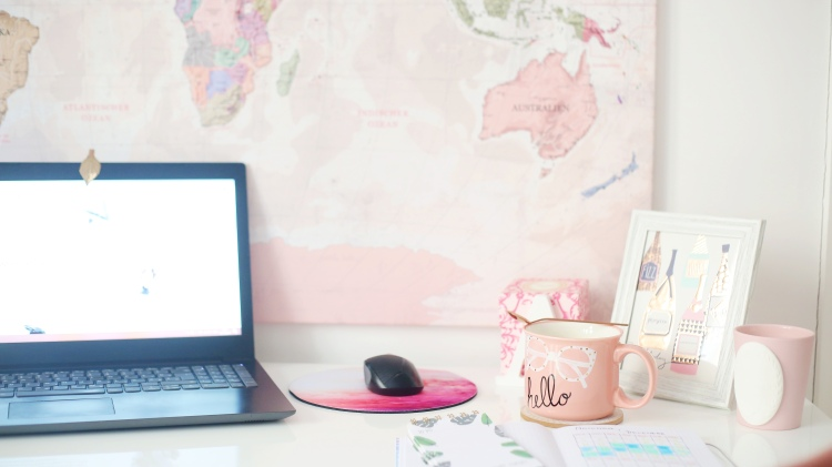 laptop on a desk with a pink map of the world, a pink mug and a notebook open