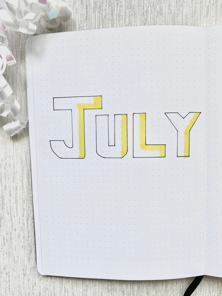 dotted journal with july on it highlighted in yellow