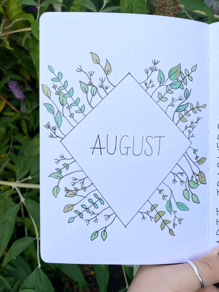 An August cover page in a archer and olive dotted journal. A diamond with flowers and leaves around