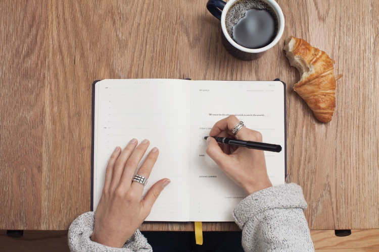An open planner on a brown desk with a lady writing in a black pen, with a coffee and croissant