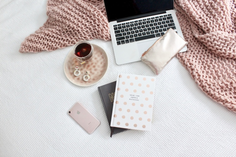 A flat lay on a bed with a macbook, two planner notebooks, a tea and an iPhone n
