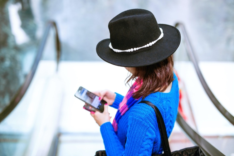 A brunette woman with a black hat in a electric bolt blue jumper holding a smart phone