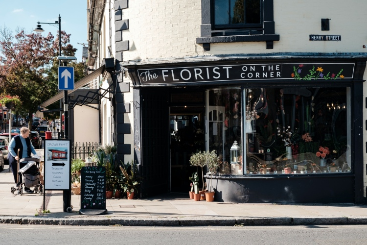 A florist called the florist on the corner with an open sign outside on a sunny day.