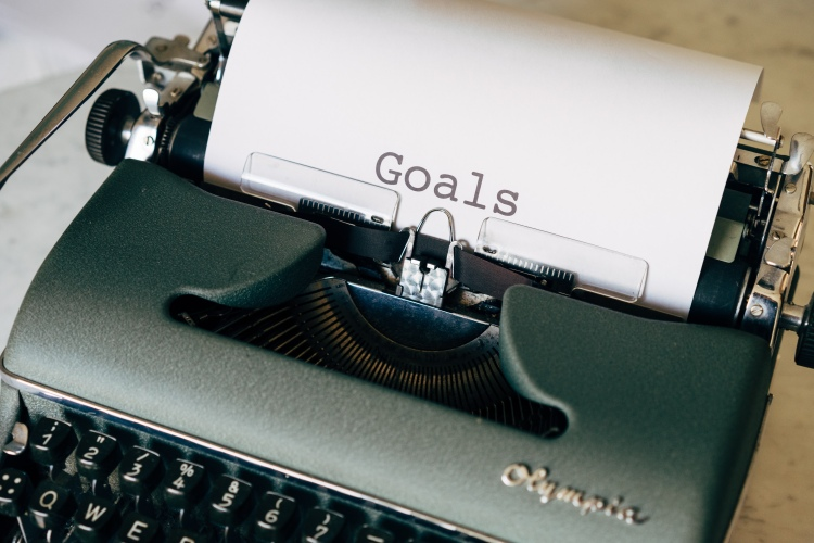 a type writer with the word goals typed on white plain paper
