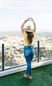 A woman with brunette hair in jeans and a yellow top stood on a balcony with a view with her hands in a heart shape