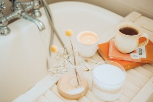 A bath with a shelf that has flowers a lit candle and a cup of warm tea that is stacked on two books.