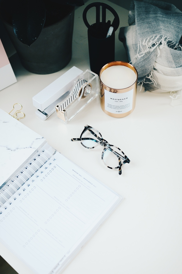 a planner open on a desk with glasses, a candle scissors, tape and a plant pot.