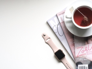 A desk with stacked magazine, a mug with fruit tea and an apple watch