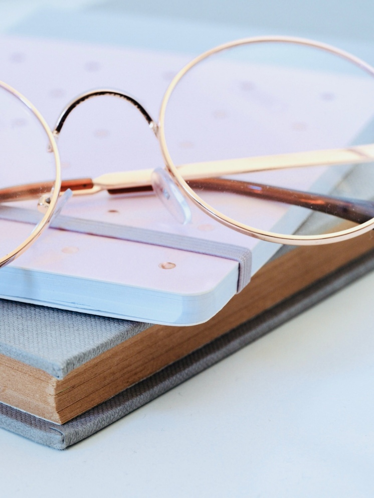 A grey notebook with a pink notebook on top with glasses