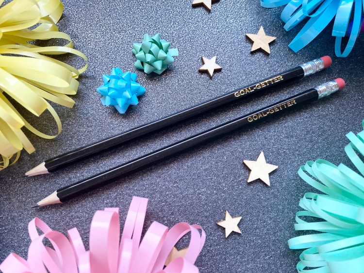 Two pencils that have goal-getter saying in gold edged into them.