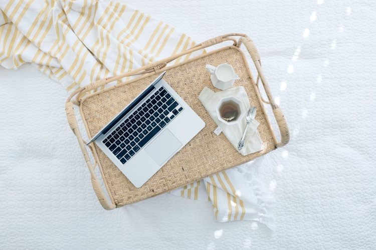 A wicker tray laying on top of a white spread with a nude and stripe scarf. On the tray it has a macbook, a cup of tea with a tea bag still in the mug with a silver spoon next to the mug. There also is a milk jug.