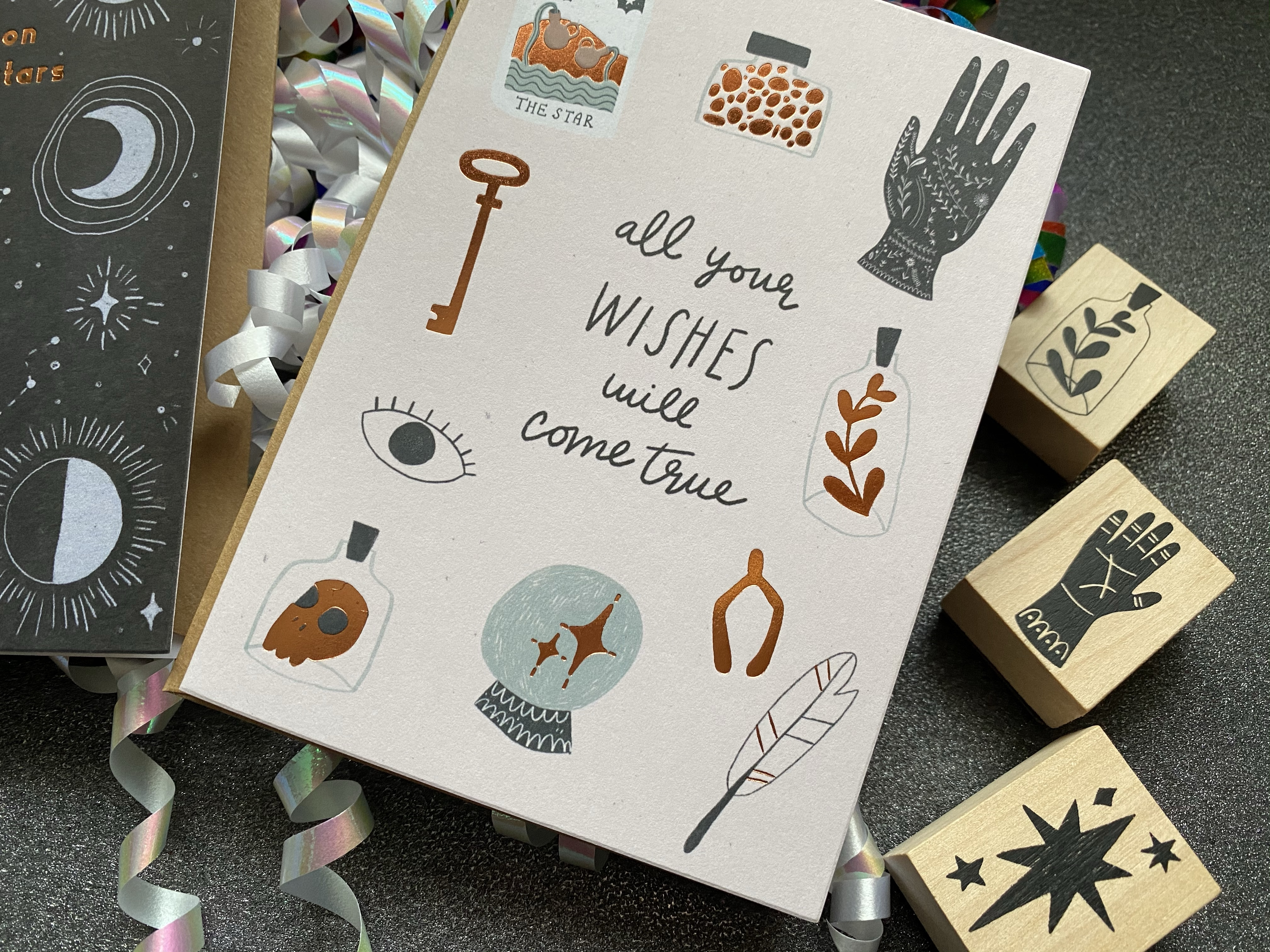 A greeting card that has pictures of an a leaf, a hand, a rose gold key and an eye. It says All Your Wishes Will Come True, with stamps on the side.
