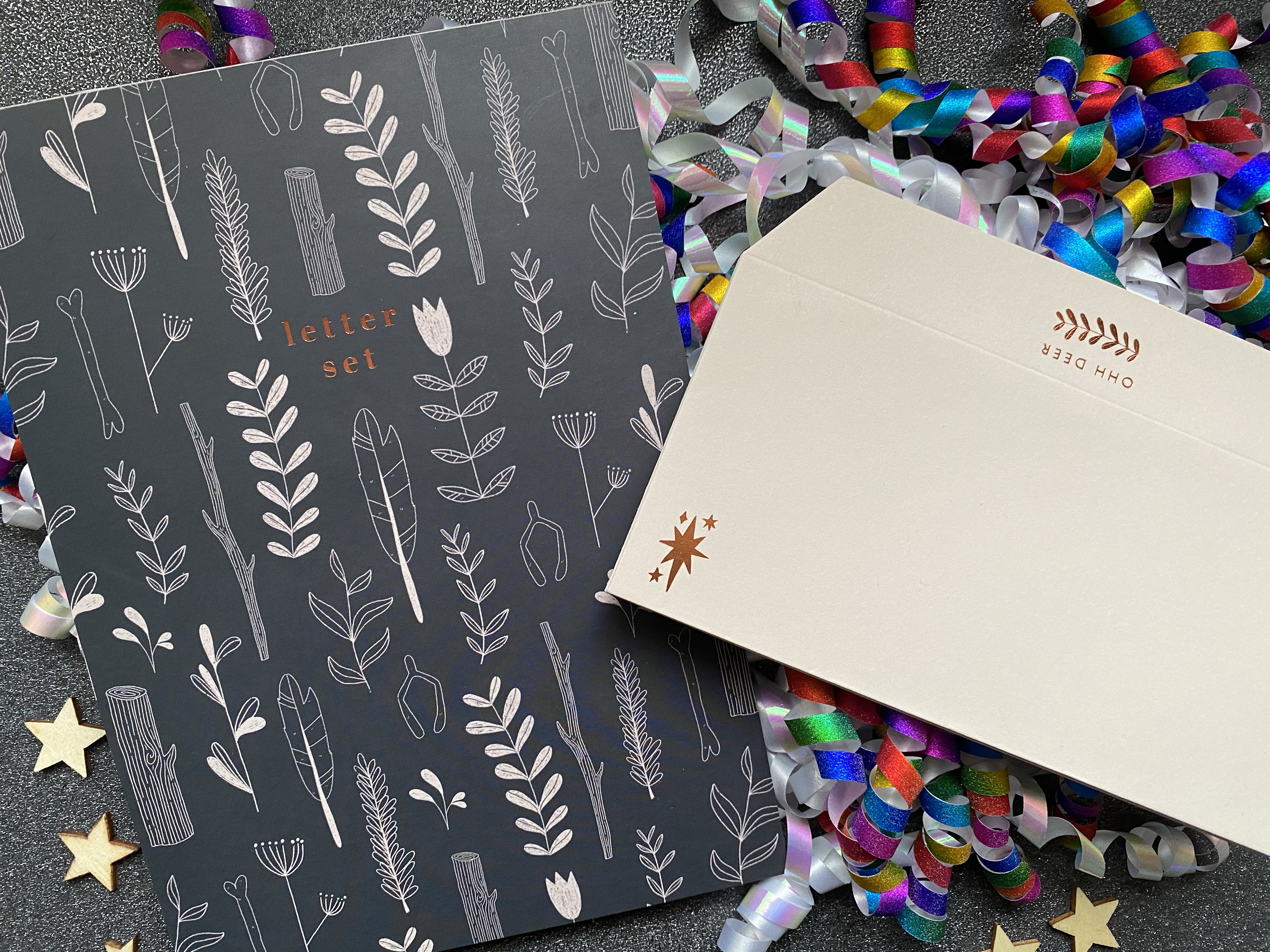 An A5 letter pad that is black with white doodles of plants and leaves, the pattern is the same as on the front of the box. There is also ivory coloured envelopes with OHH DEER logo and a star design both in rose gold.