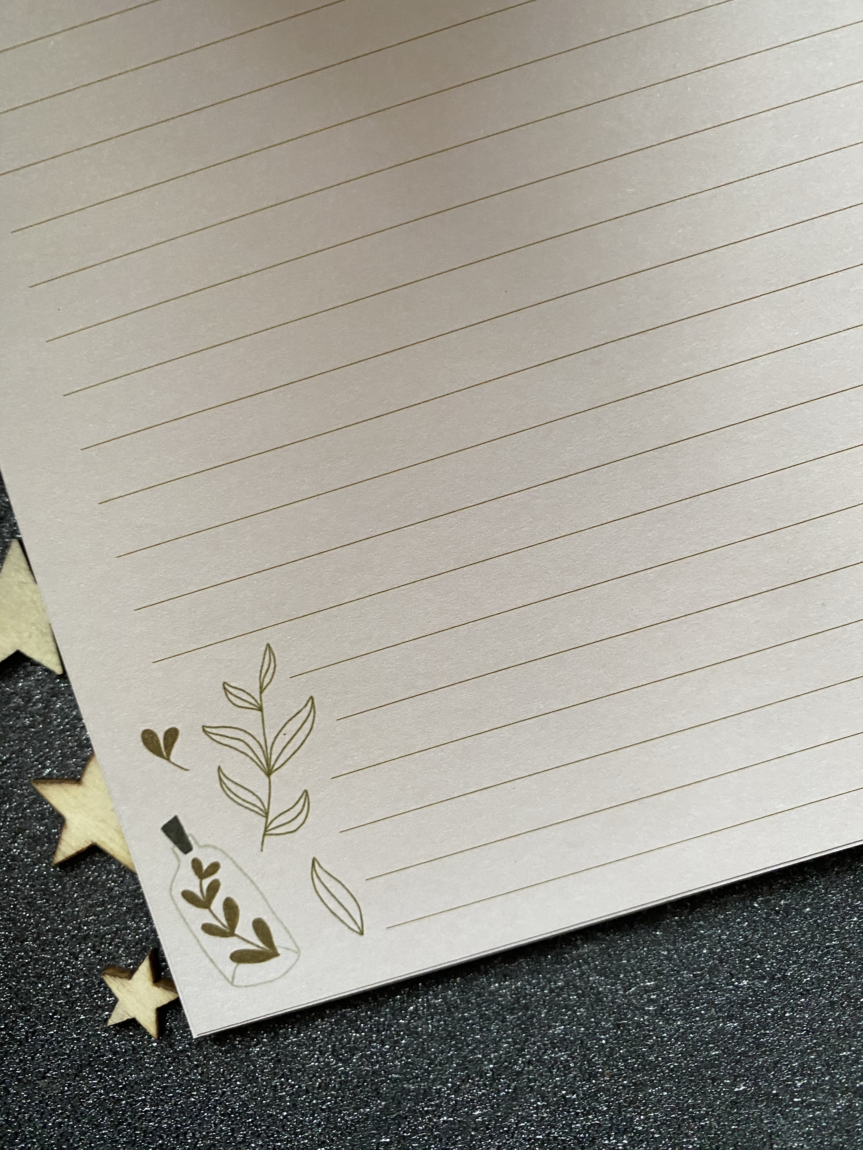 A lined pad with green lines with a design of leaves and leaves in a glass bottle on the right corner of each page.