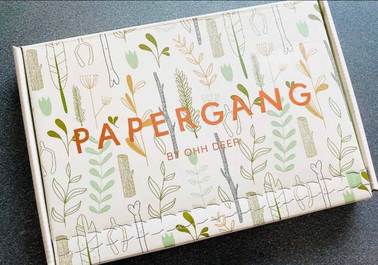 A Papergang subscription box with different leaves and wood. Papergang and OHH DEER is written in rose gold lettering.
