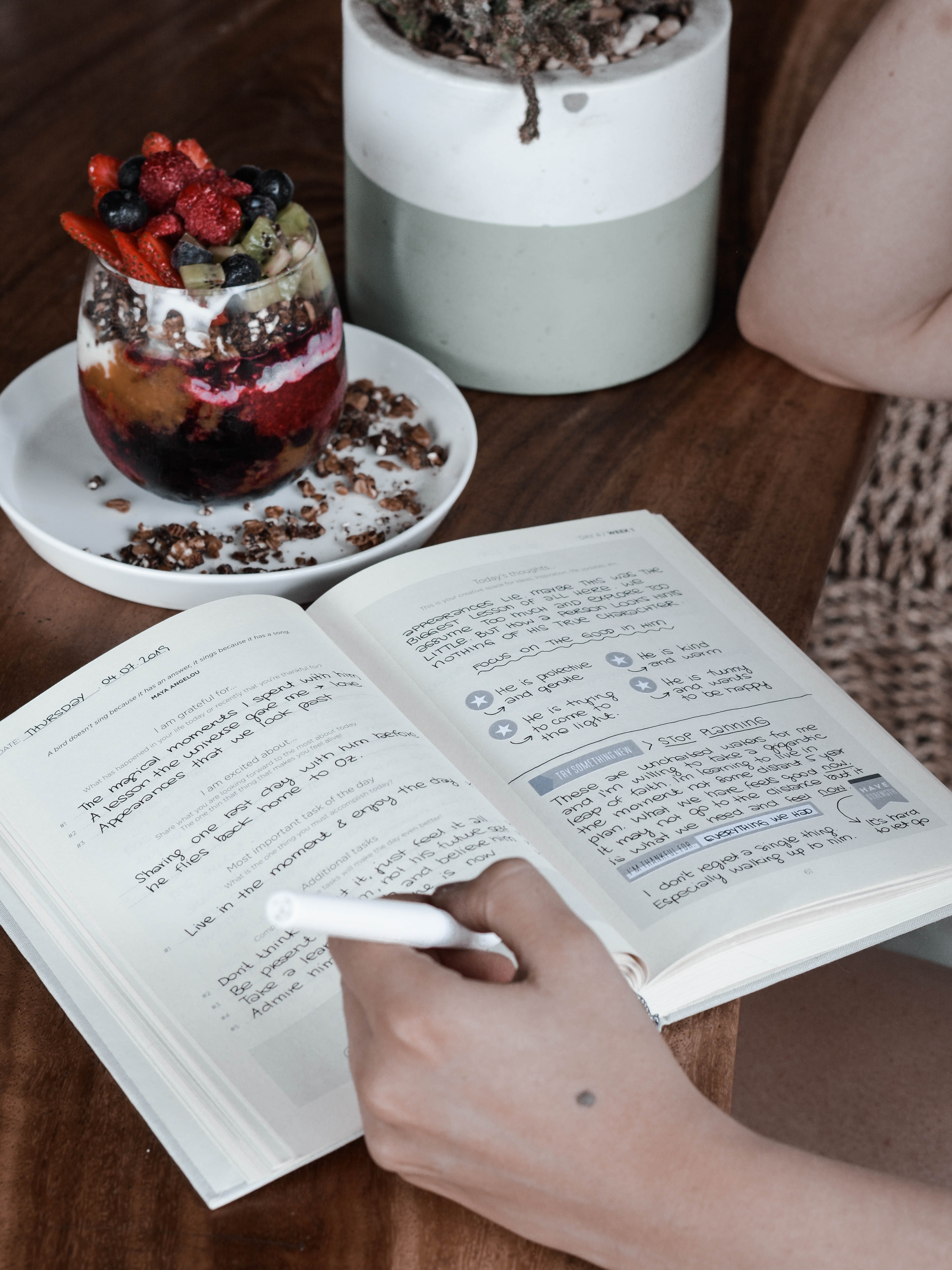 A gratitude journal open with a person holding a white pen writing on the page, the book already has writing in. Next to the book is a dessert with fruit in a small glass and a faux plant next the glass.