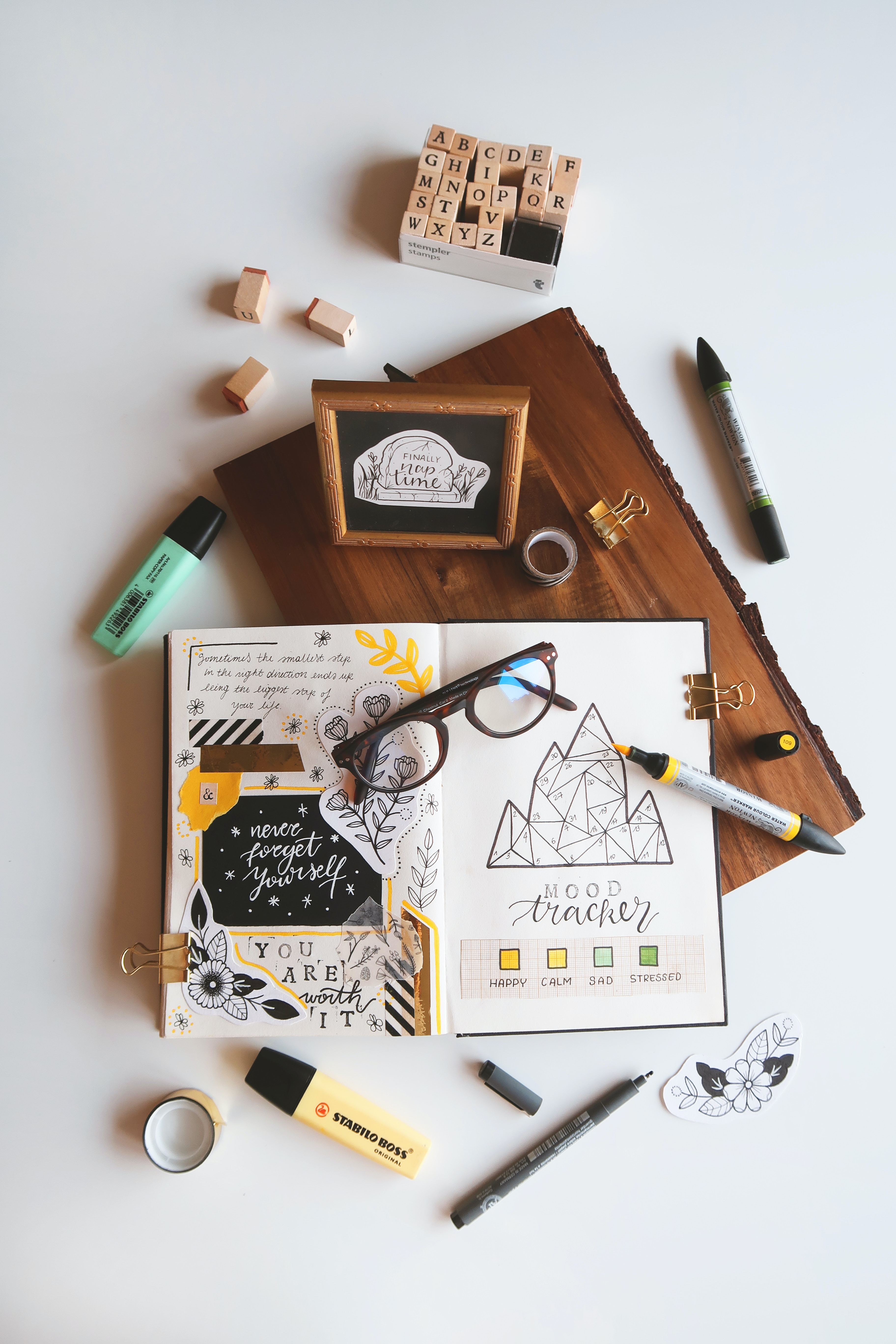 On a white table is a block of wood, on top of the wood is an open bullet journal. The bullet journal has scrapbooking designs on the left page and the right page has a mood tracker. Next to the bullet journal there is washi tapes, stamps and pens.