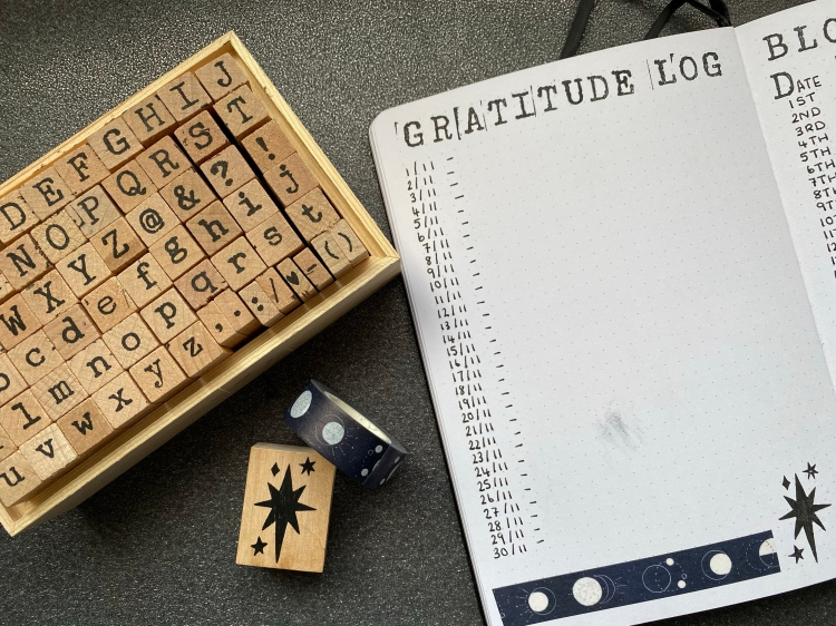 A gratitude log page designed in my bullet journal. The lettering is designed in stamps, with black and white moon washi tape and a star stamp. Next to my bullet journal there is a box of alphabet stamps, black and white moon washi and a star stamp.