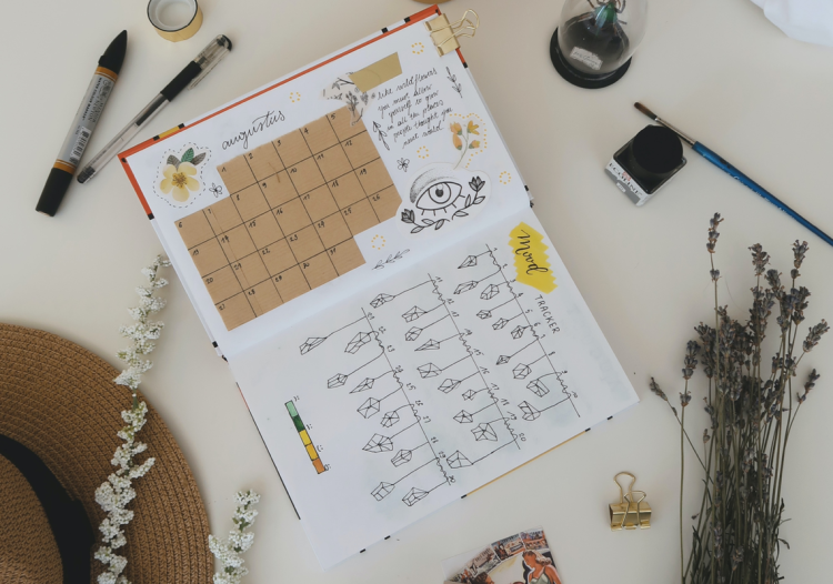 On a white desk there is dried flowers and a brown hat. There is a bullet journal opened on a monthly spread and a mood tracker. Next to the bullet journal there is a pot of black ink and a paint brush.
