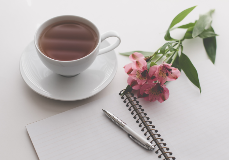 On top of the white desk is a white cup and saucer with tea next to a lined coiled notebook and white and silver pen. Lying across the notebook is some pink flowers.