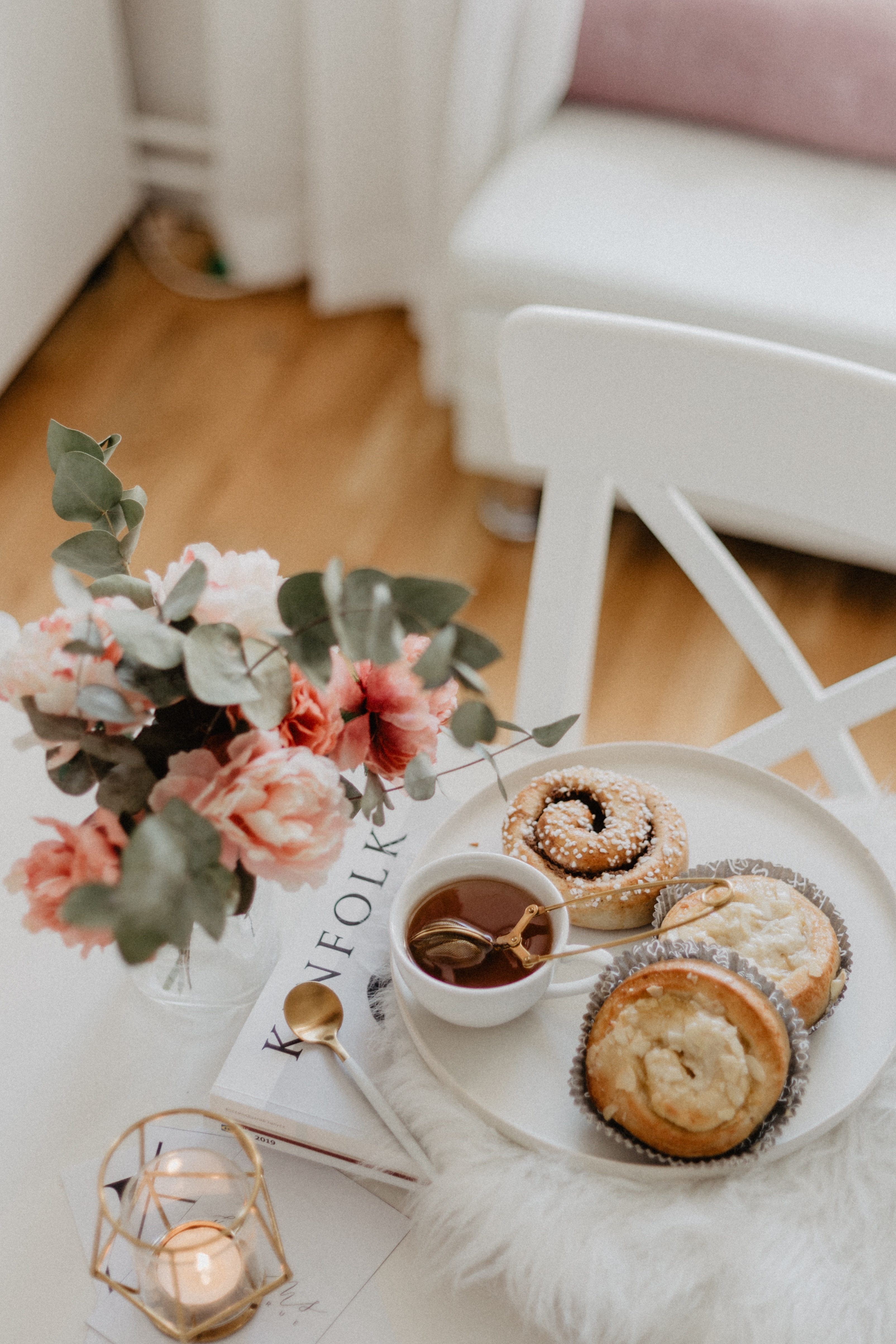 There is a white table and chair in the middle of the image. On the white table is a vase with pink flowers in. Next to the flowers is a pile of magazines with a plate of pastries and cakes on with a tiny mug of tea. There is gold
