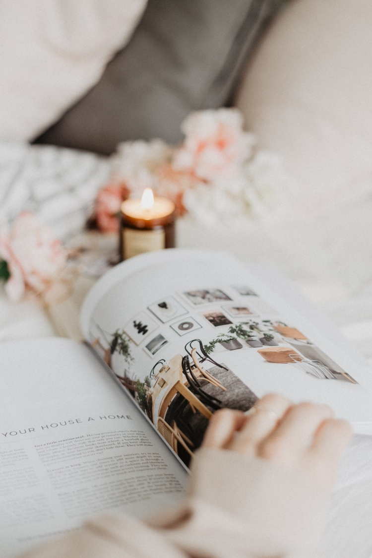 An open magazine on a bed with a lit candle and flowers with a hand flicking through.