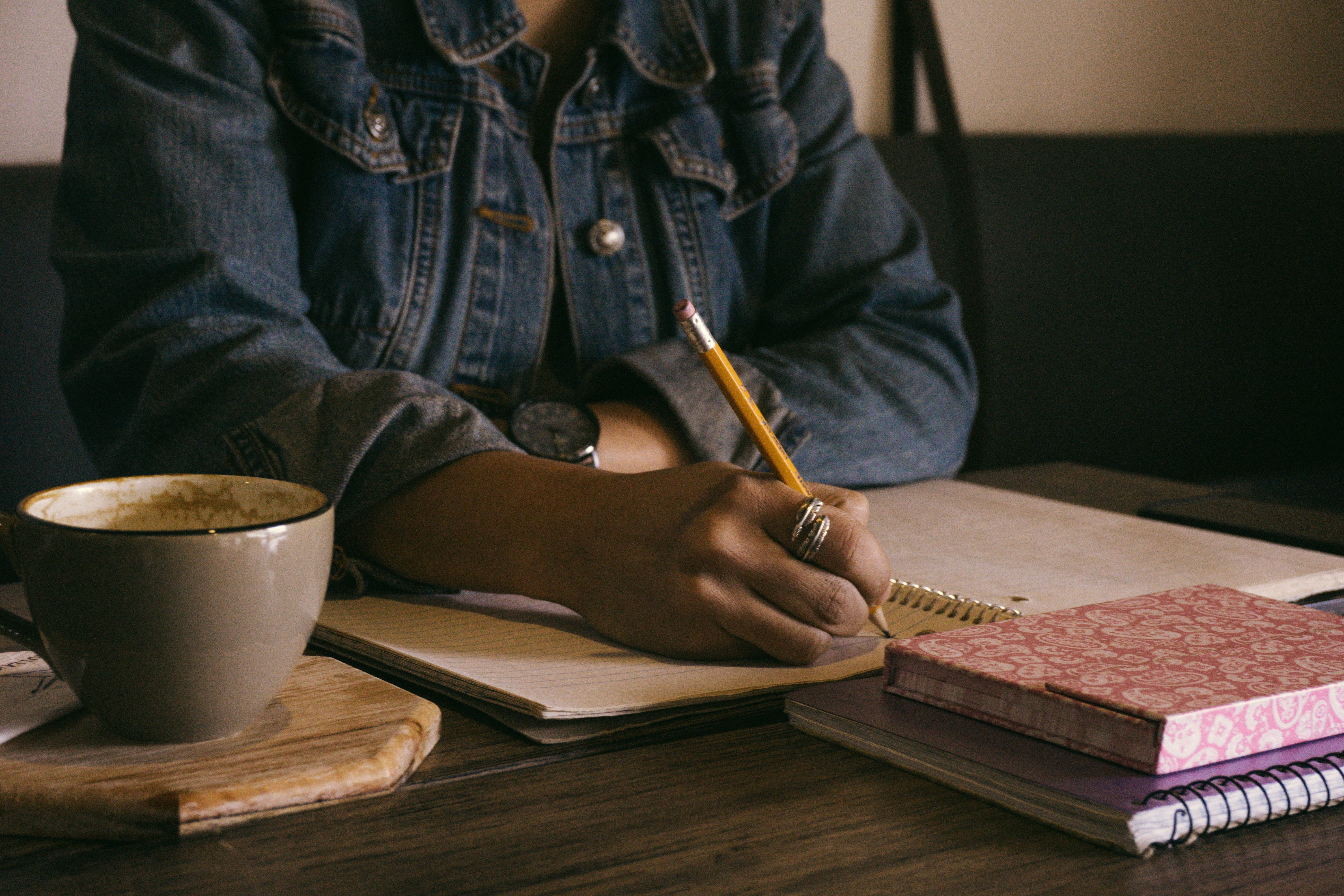 Woman in a dark denim jacket with a black watch on her left wrist, is writing with a pencil in a lined notebook. Next to the notebook is two notebook pilled up together. Next to her is a mug of her drink and a wooden coaster.