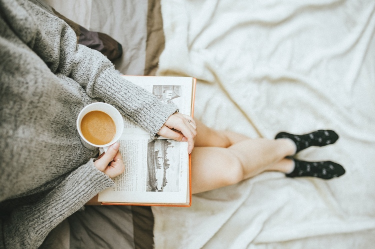 A woman sat on a bed in a grey super and black and white socks. She is hoping a book open and a hot hot drink in a white mug