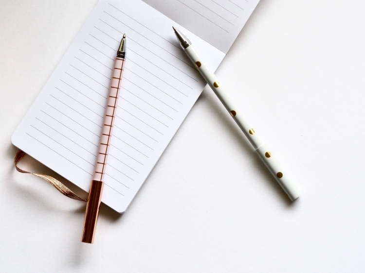An A6 flip up notebook that has lined pages and on top of the pad is two bullet point pens. One pen is pink with rose gold squares and the other pen is white with gold dots.