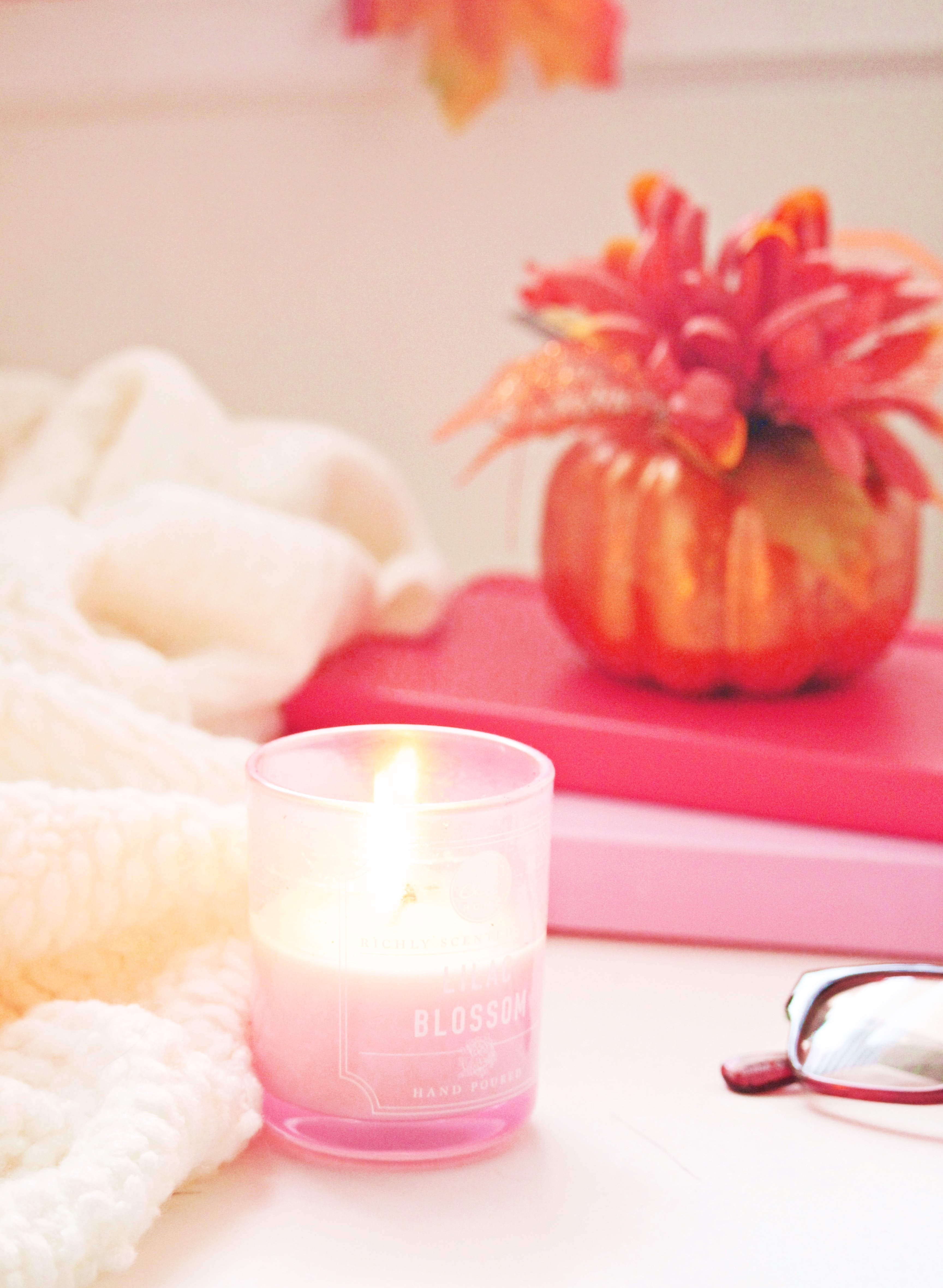 Two pinks book piled up with a faux pink plant. There is a pink candle lit next to a white blanket