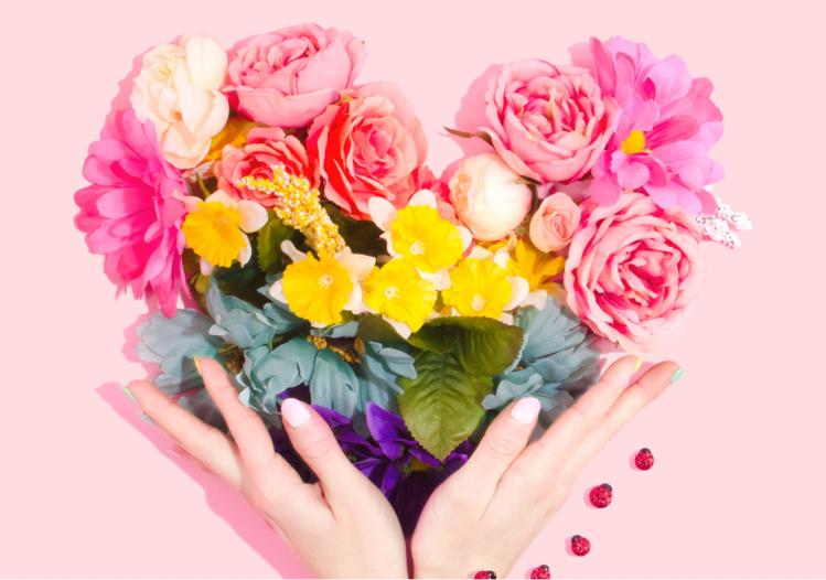 A heart shaped out of flowers. The flowers are a range of colours and types included baby pink roses and pink daisies. There is a lady hands holding the bottom of the heart and she has white coloured nails and next to her hand is lady birds.