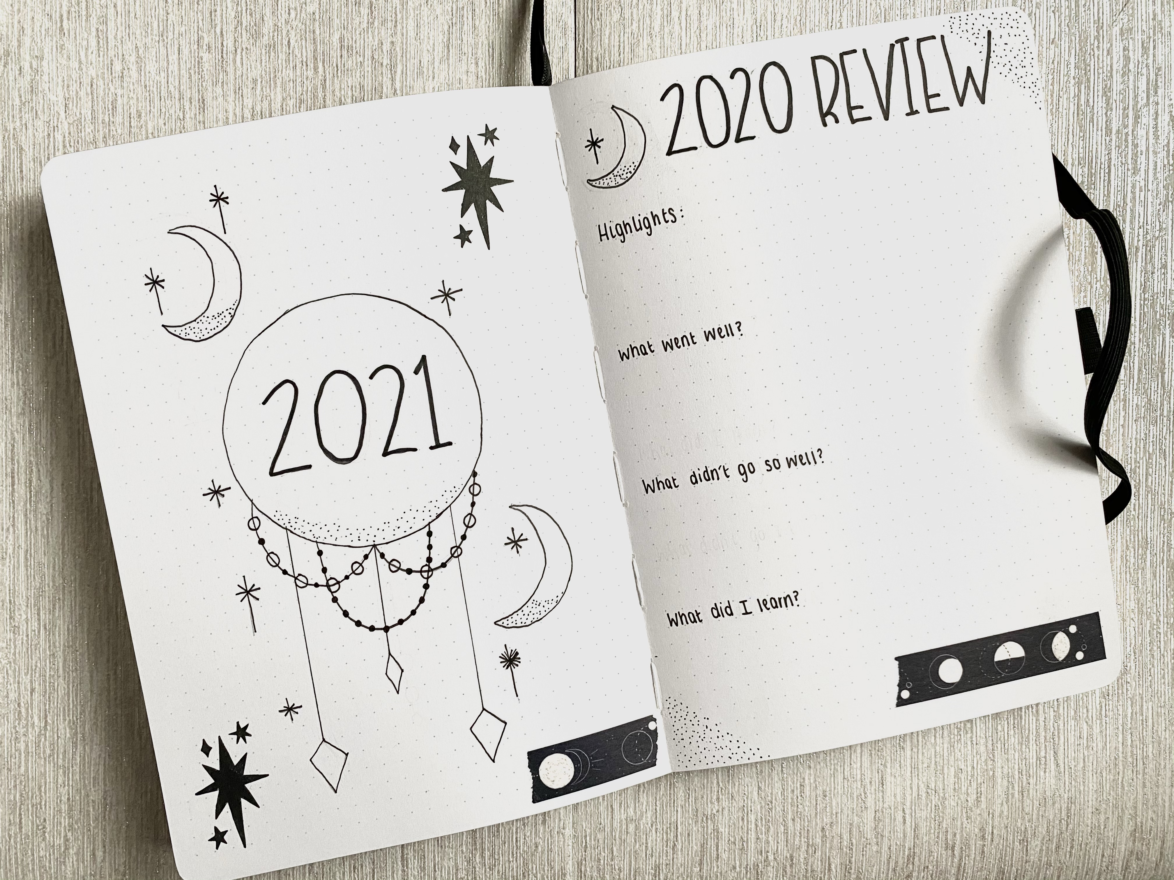 A bullet journal set up for 2021 using a black and white theme. The pages have moons, stars and moon washi tape on them. The first page on the left is a cover page and the page on the right is a review of 2020.
