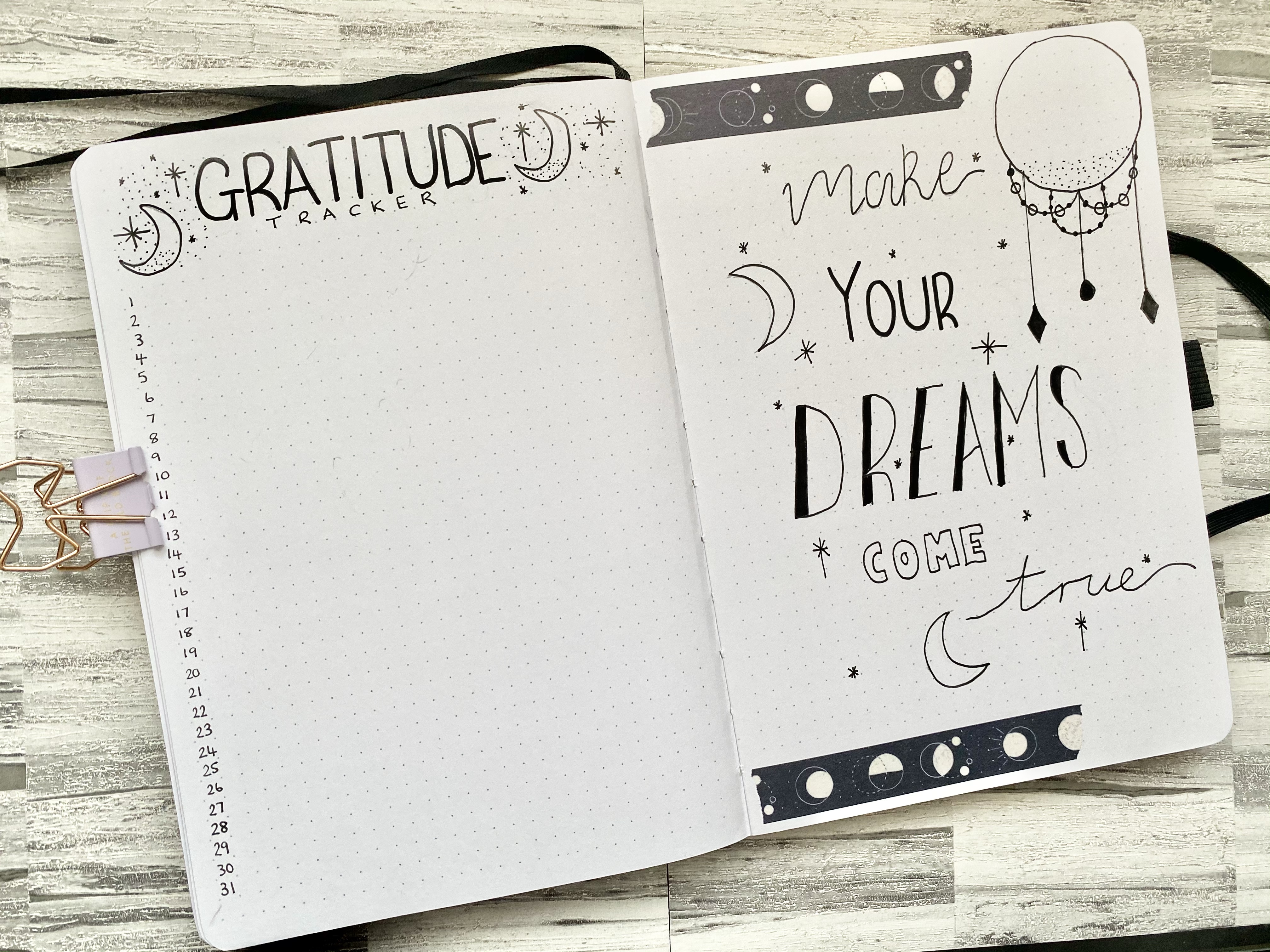 """This is an open double page spread in an Archer & Olive bullet journal. On the left page is a gratitude tracker which is decorated with little stars and moon doodles. It has the list of days and a space for me to write a sentence each day about what I am grateful for. On the right side page is a quote that says """"Make your dreams come true"""" is different fonts and all in black pen. It is decorated with stars, circles, moons, diamonds and black and white moon washi tape at the top and bottom of the page."""