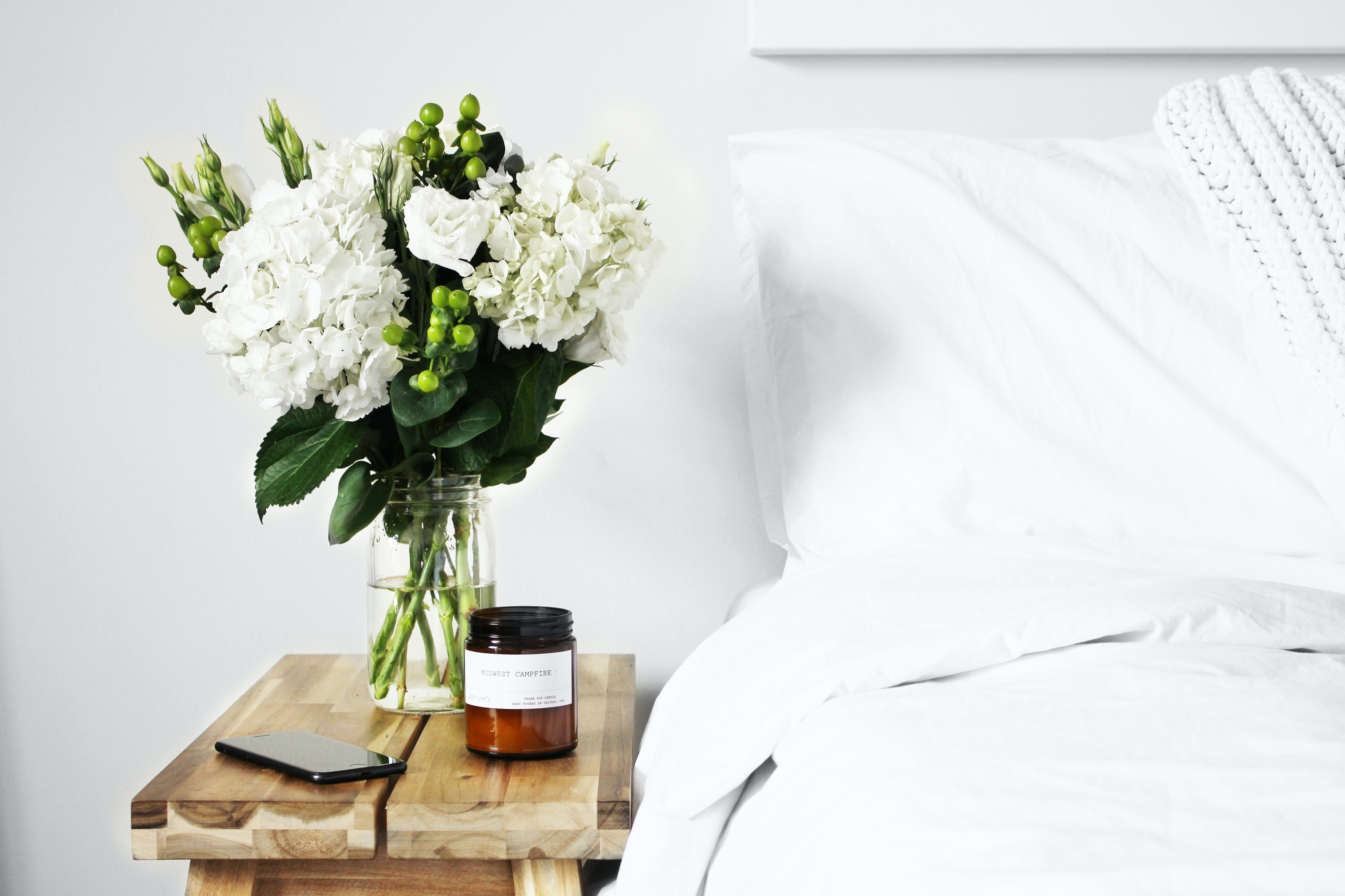 A bed with white duvet and pillows is next to wooden panels used as a bedside table. On top of the bedside table is a bunch of white flowers in a clear glass vase. Next to the vase is a black phone and a amber jar that has a candle.
