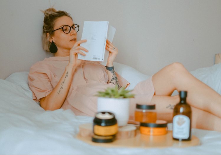 A blonde haired woman is lying on a bed that has white sheets and she is wearing a long blush pink top. On the bed is a wooden tray that has lotions and serums for self care with a faux plant in a white pot.