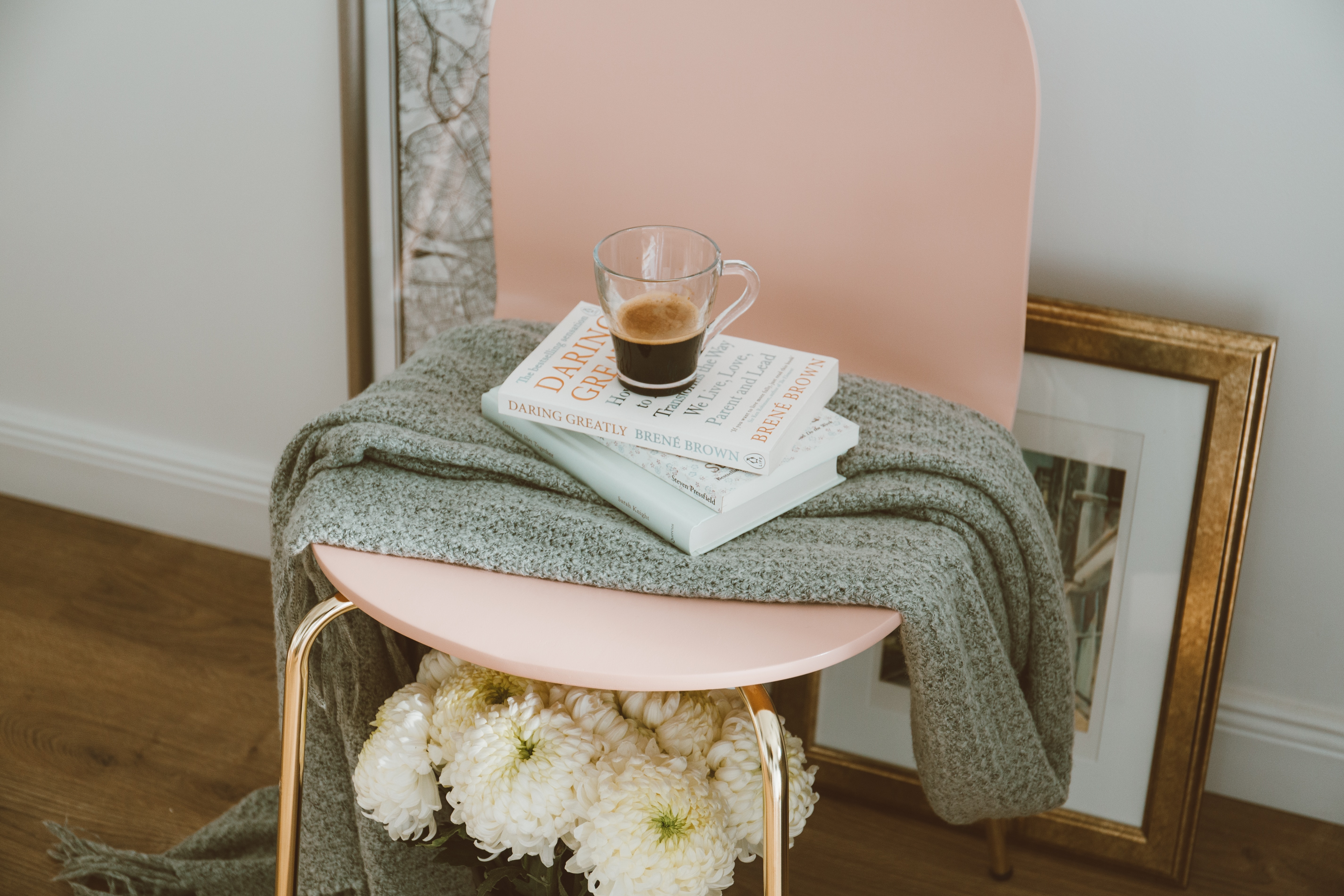 A blush pink chair with gold legs is stood upon dark wooden floors. Underneath the chair is a bunch of white flowers. On top of the chair is a grey throw, three books and on top of the books is a black coffee in a clear glass mug.