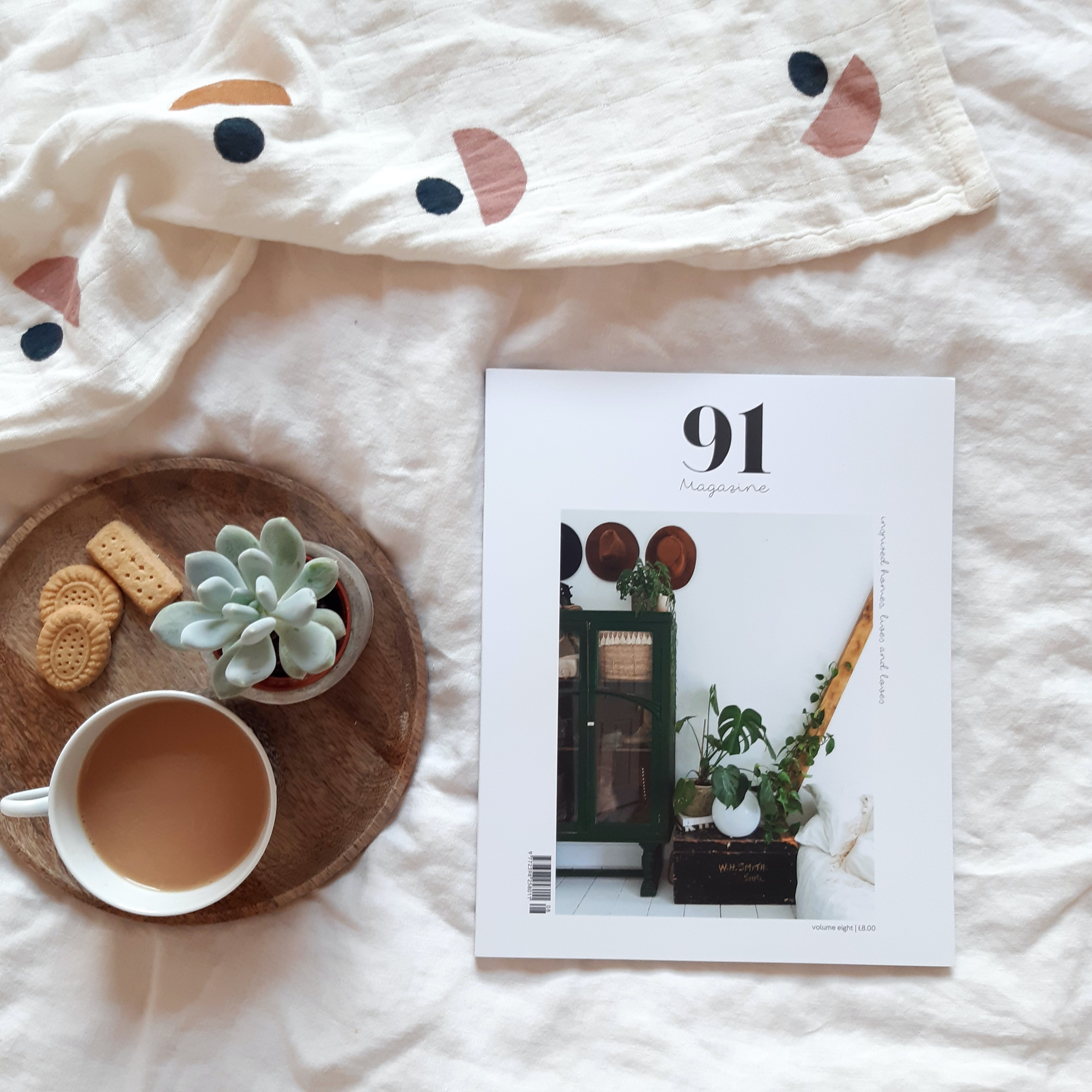 On top on white sheets is a 91 magazine. Next to the magazine is a circle wooden plate that has a faux plant, a mug of tea and three biscuits.
